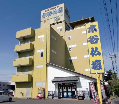 広い駐車場を完備した黄色い看板が目印の店舗外観
